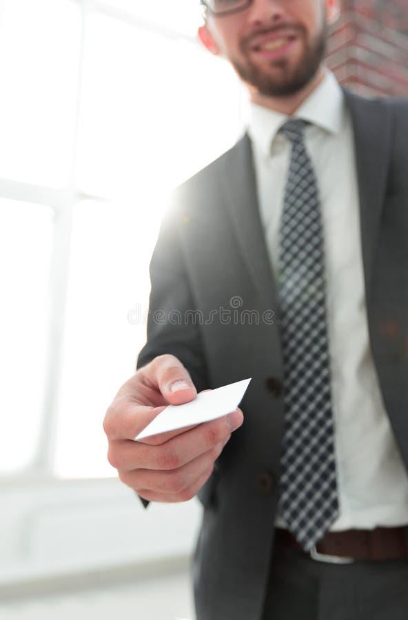 Hombre de negocios que da una tarjeta Foto del primer en oficina del desván foto de archivo