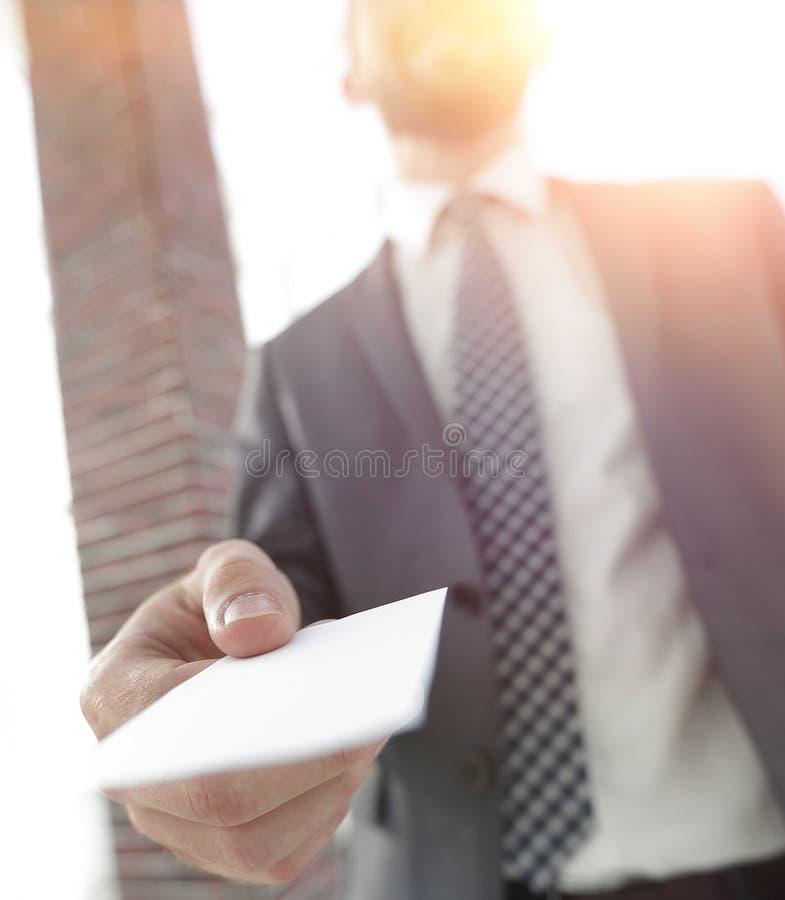 Hombre de negocios que da una tarjeta Foto del primer en oficina del desván imagenes de archivo