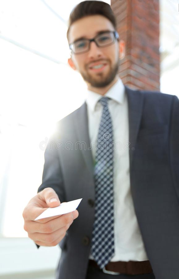 Hombre de negocios que da una tarjeta Foto del primer en oficina del desván fotografía de archivo