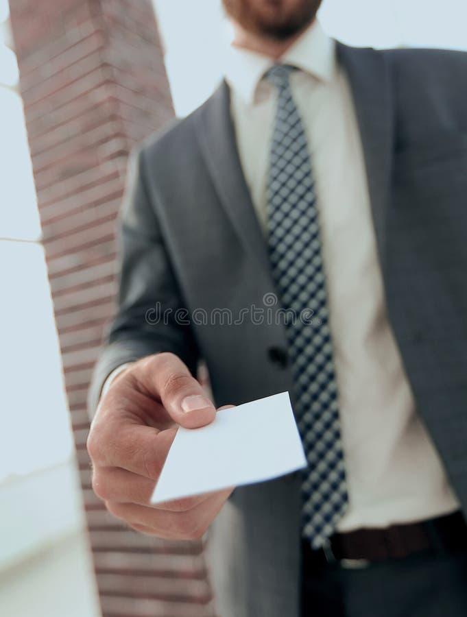 Hombre de negocios que da una tarjeta Foto del primer en oficina del desván fotos de archivo