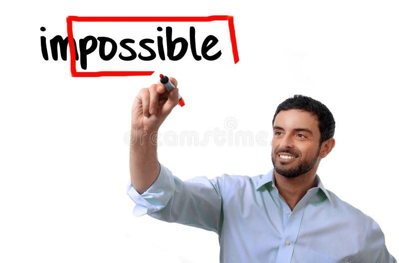 Hombre de negocios que da vuelta a palabra imposible en la escritura posible con el marcador rojo fotos de archivo libres de regalías