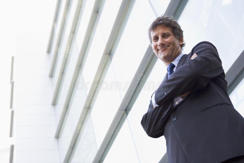 Hombre de negocios que defiende al aire libre la sonrisa constructiva foto de archivo