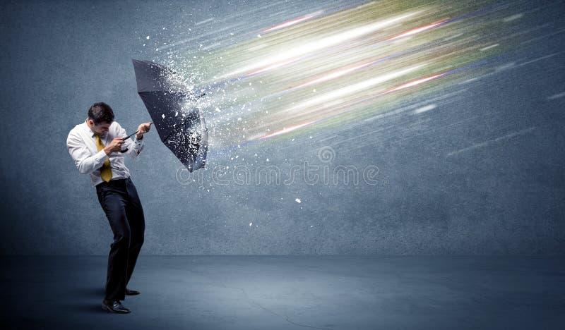 Hombre de negocios que defiende haces luminosos con concepto del paraguas imagen de archivo