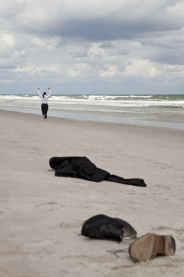 Hombre de negocios que deja la ropa en la playa que se ejecuta lejos foto de archivo libre de regalías