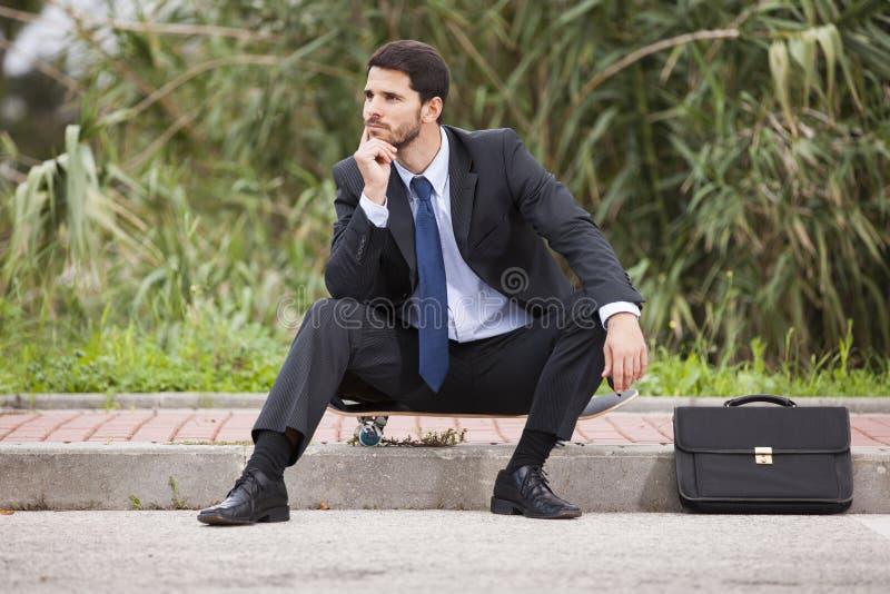 Hombre de negocios que descansa con su monopatín fotos de archivo