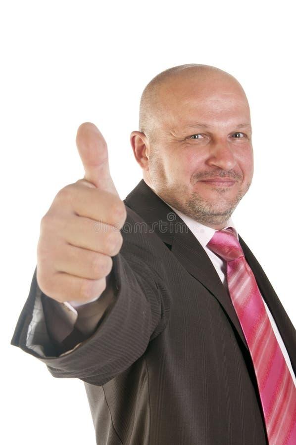 Hombre de negocios que detiene el pulgar. foto de archivo