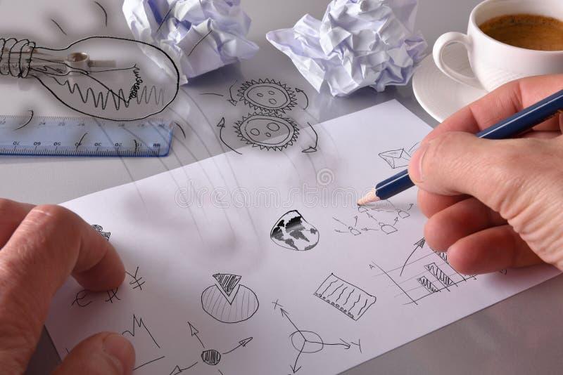 Hombre de negocios que dibuja conceptos relevantes del negocio en negocio de la hoja fotos de archivo