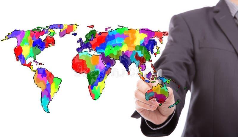 Hombre de negocios que dibuja el mapa colorido del mundo fotografía de archivo