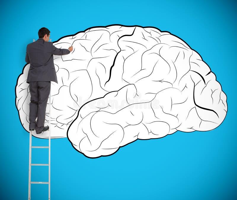 Hombre de negocios que dibuja un cerebro en una pared gigante fotografía de archivo libre de regalías