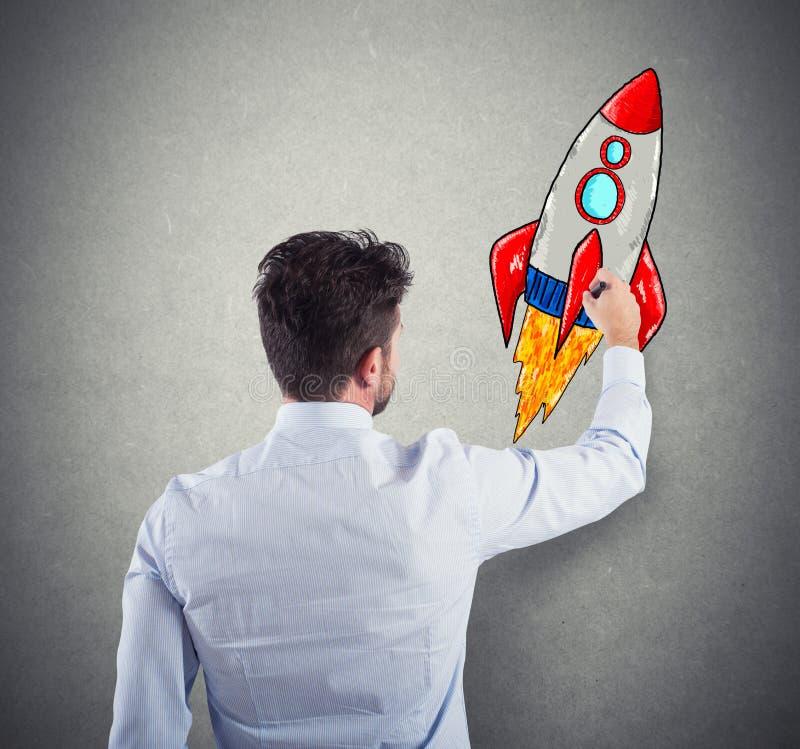 Hombre de negocios que dibuja un cohete Concepto de mejora del negocio y de inicio de la empresa fotos de archivo libres de regalías