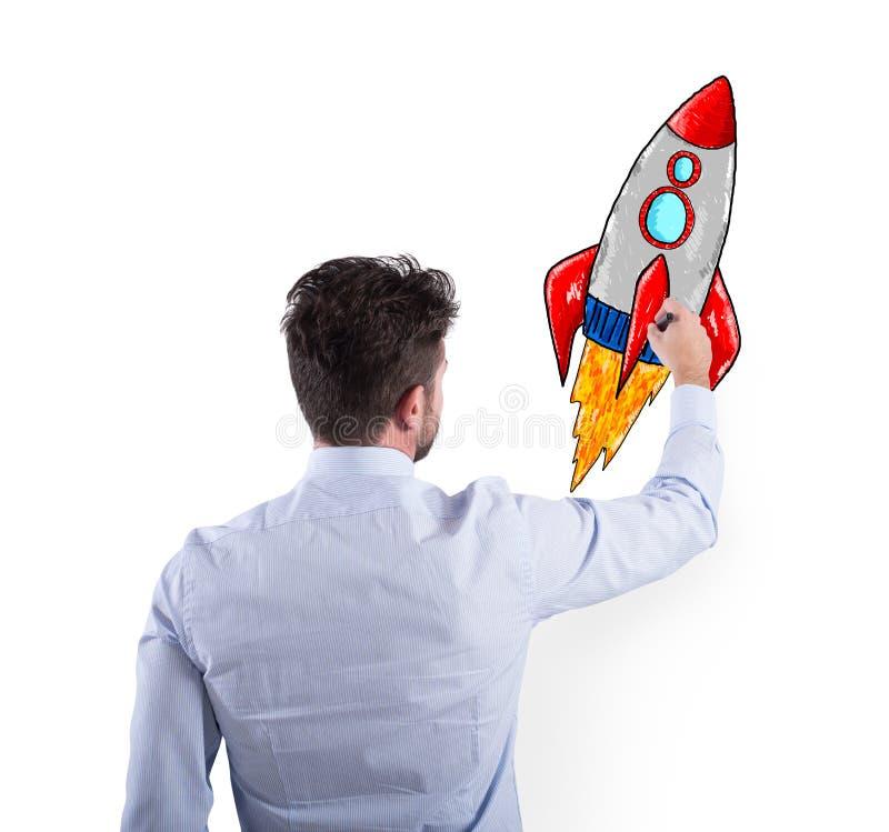 Hombre de negocios que dibuja un cohete Concepto de mejora del negocio y de inicio de la empresa fotografía de archivo