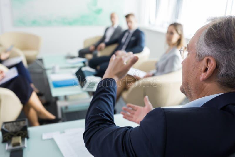 Hombre de negocios que discute con los colegas en sala de reuni?n fotos de archivo libres de regalías