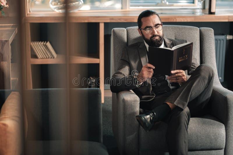 Hombre de negocios que disfruta de la rotura del trabajo mientras que lee la Sagrada Biblia foto de archivo