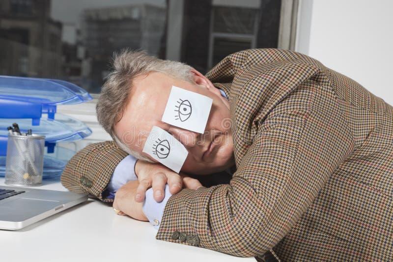 Hombre de negocios que duerme con las notas pegajosas sobre ojos en el escritorio en oficina imágenes de archivo libres de regalías