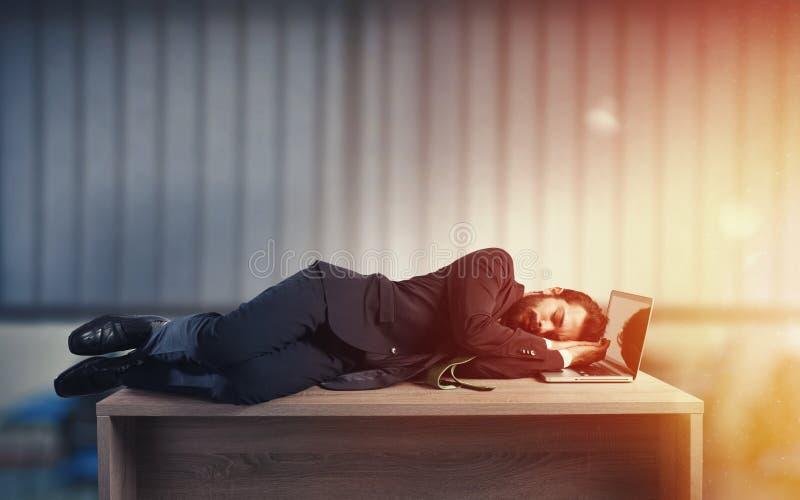 Hombre de negocios que duerme sobre un escritorio debido trabajar demasiado foto de archivo