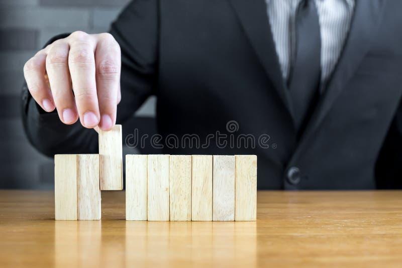 Hombre de negocios que elige el bloque de madera, concepto del reclutamiento foto de archivo