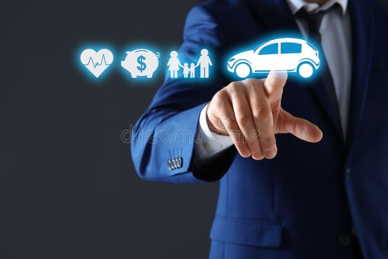 Hombre de negocios que elige el icono del coche en la pantalla virtual contra fondo oscuro foto de archivo libre de regalías