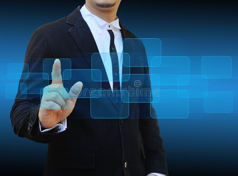 Hombre de negocios que empuja el botón manualmente en un interfaz de la pantalla táctil fotos de archivo libres de regalías