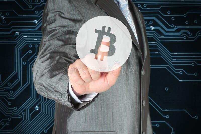 Hombre de negocios que empuja el botón virtual con el símbolo de Bitcoin fotografía de archivo