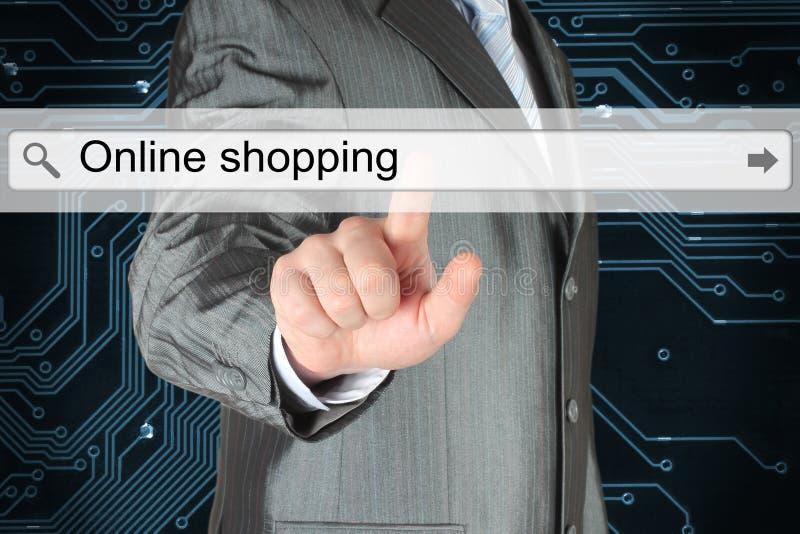 Hombre de negocios que empuja la barra virtual de la búsqueda con palabras en línea de las compras foto de archivo