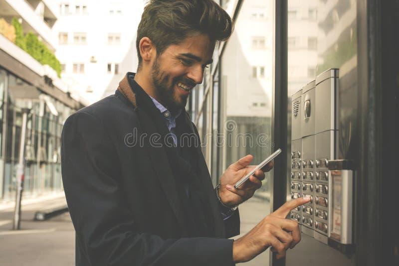Hombre de negocios que empuja la parte inferior en mobi del edificio y de la tenencia foto de archivo libre de regalías
