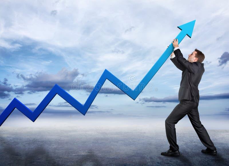 Hombre de negocios que empuja una flecha gráfica hacia arriba imagenes de archivo