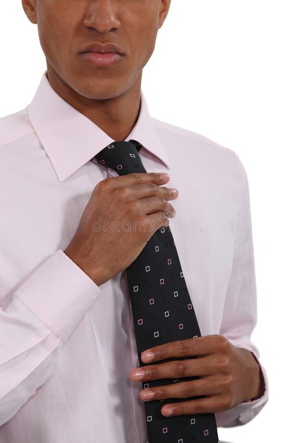 Hombre de negocios que endereza el suyo lazo fotos de archivo