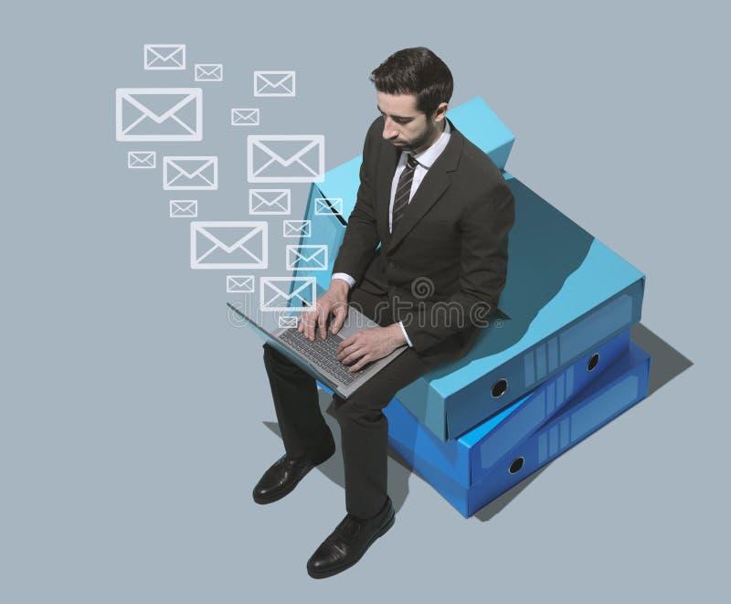 Hombre de negocios que envía email con su ordenador portátil foto de archivo libre de regalías
