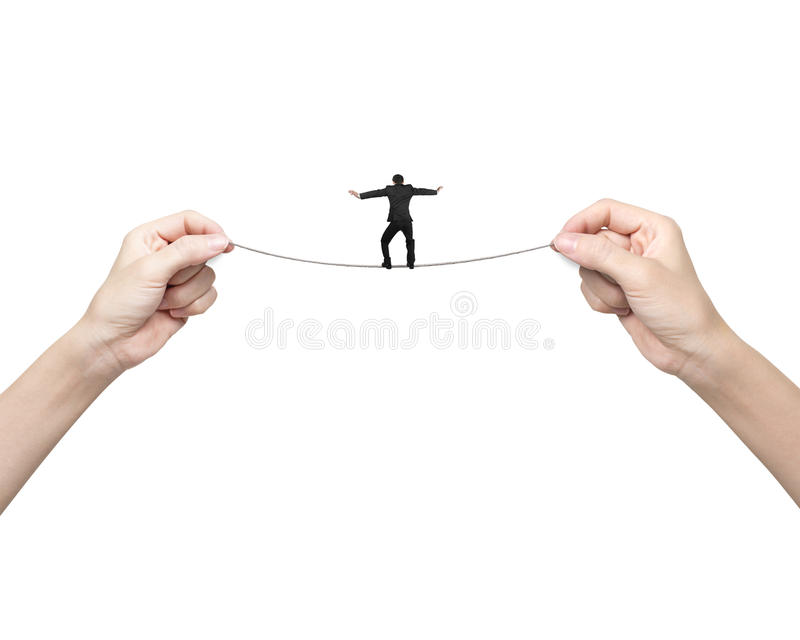 Hombre de negocios que equilibra en cuerda tirante con sostenerse de las manos de la mujer dos imágenes de archivo libres de regalías