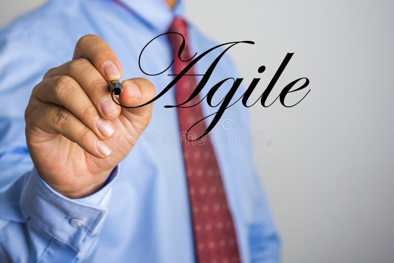 Hombre de negocios que escribe palabra ágil en la pantalla virtual foto de archivo