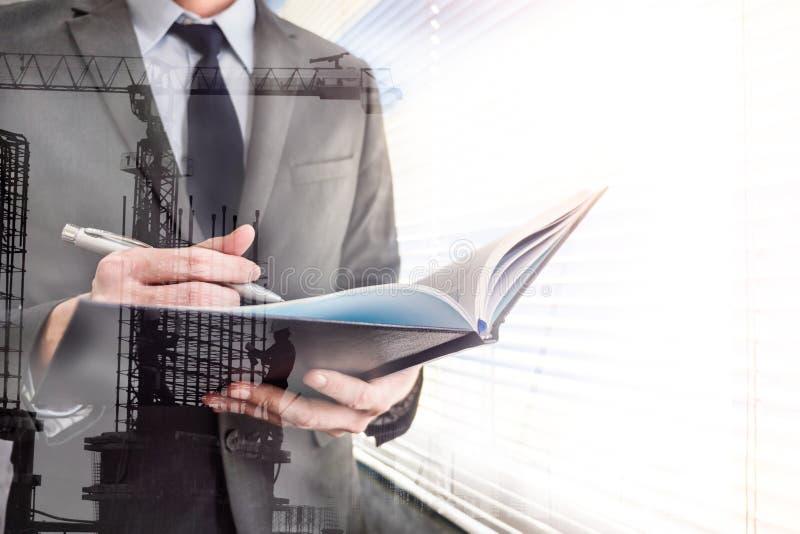 Hombre de negocios que escribe un ciertos datos en cuaderno con el sitio de la construcción de edificios foto de archivo