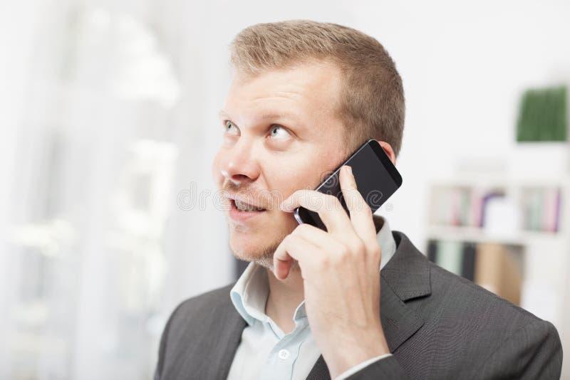 Hombre de negocios que escucha con la anticipación una llamada foto de archivo libre de regalías
