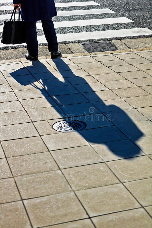 Hombre de negocios que espera para cruzar el camino fotos de archivo