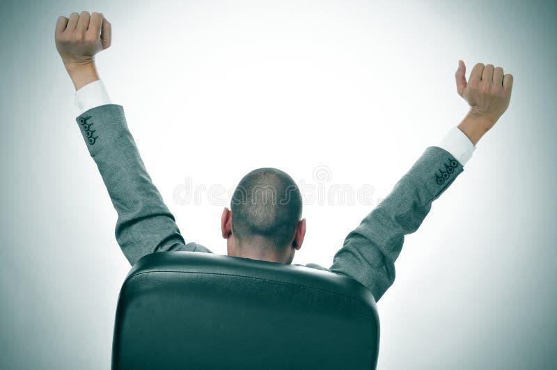 Hombre de negocios que estira en su silla de la oficina imagen de archivo libre de regalías
