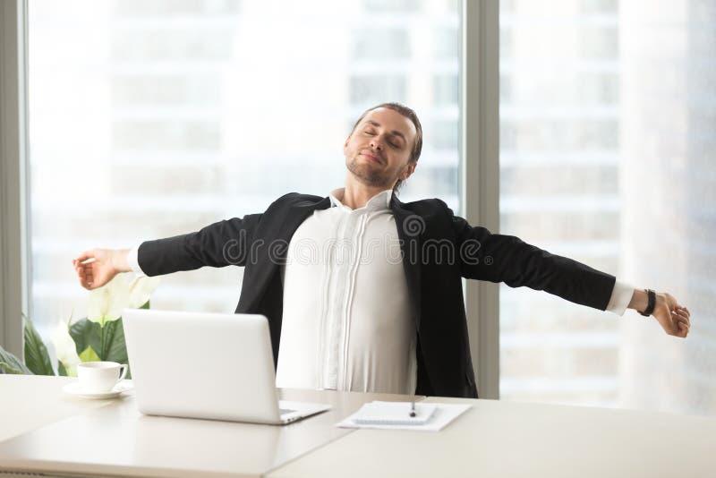 Hombre de negocios que estira hacia fuera en el escritorio con el ordenador portátil imagenes de archivo