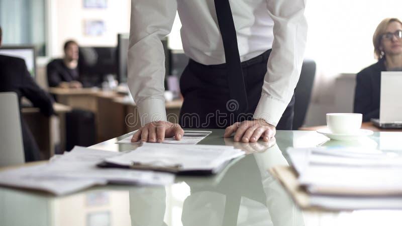 Hombre de negocios que estudia el contrato, empleados de oficina que trabajan en el fondo, vida ocupada imágenes de archivo libres de regalías