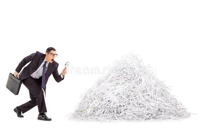 Hombre de negocios que examina una pila de papel destrozado imagen de archivo