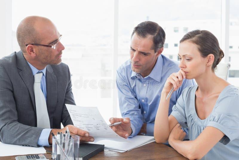 Hombre de negocios que explica el contrato a los socios comerciales fotografía de archivo libre de regalías
