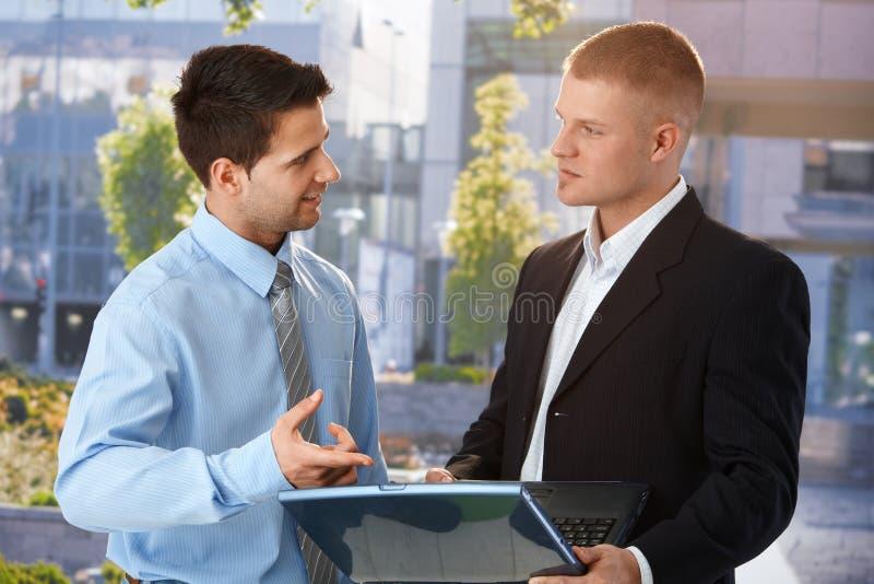 Hombre de negocios que explica el trabajo del ordenador del colega foto de archivo