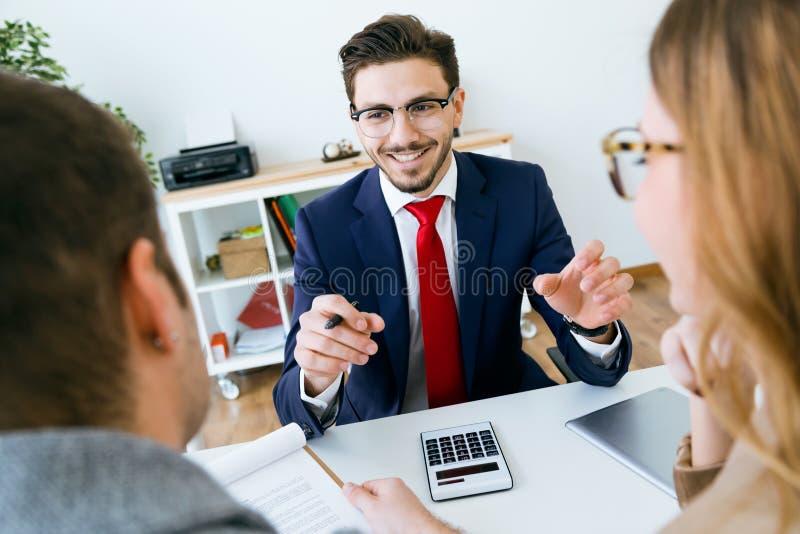 Hombre de negocios que explica términos del contrato a sus clientes en la oficina imagen de archivo