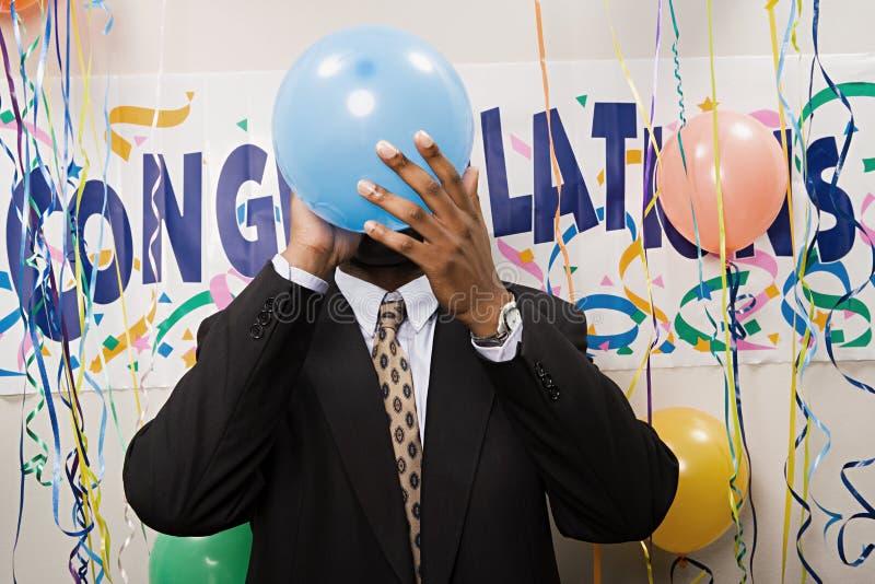 Hombre de negocios que explota un globo imagen de archivo libre de regalías