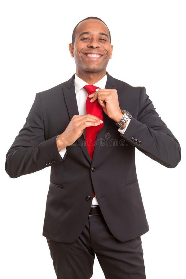Hombre de negocios que fija el suyo lazo imagen de archivo