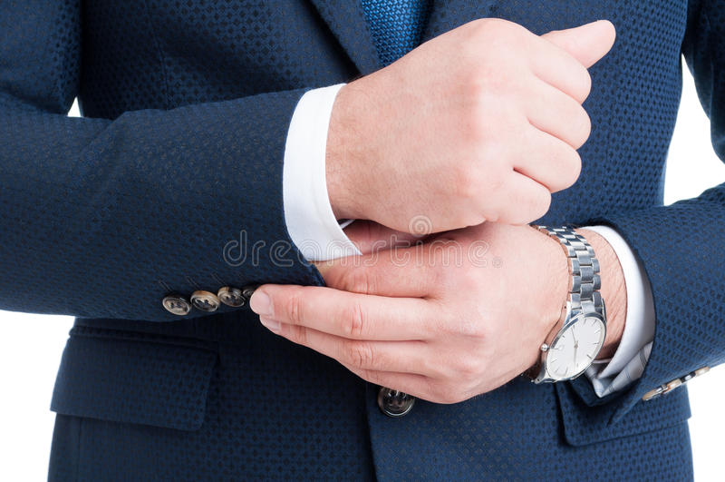 Hombre de negocios que fija y que ajusta la manga blanca de la camisa bajo s azul imagenes de archivo