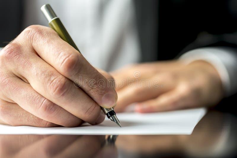 Hombre de negocios que firma o que escribe un documento fotografía de archivo libre de regalías