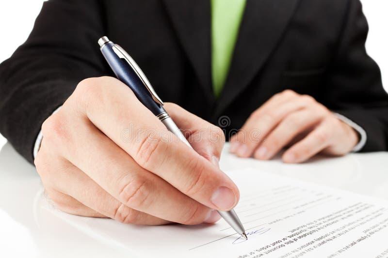 Hombre de negocios que firma un documento. imagenes de archivo