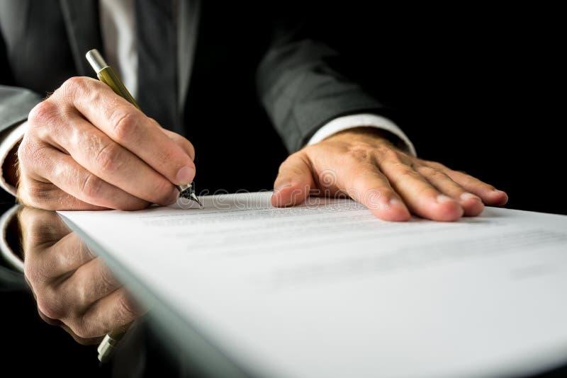 Hombre de negocios que firma un documento de papel fotos de archivo libres de regalías