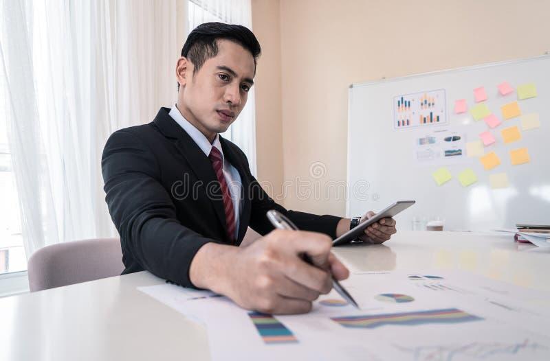 Hombre de negocios que firma un documento en la tabla de la oficina imagen de archivo libre de regalías