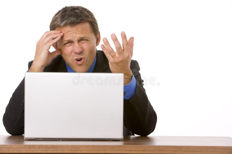Hombre de negocios que frunce el ceño mientras que mira la computadora portátil fotografía de archivo