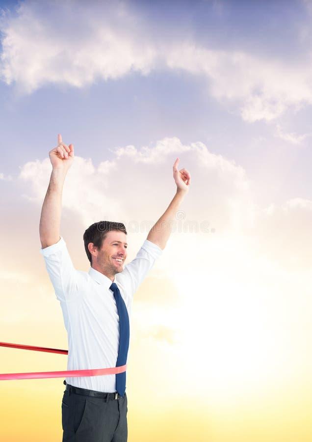 Hombre de negocios que gana la carrera contra el cielo en el fondo imagenes de archivo