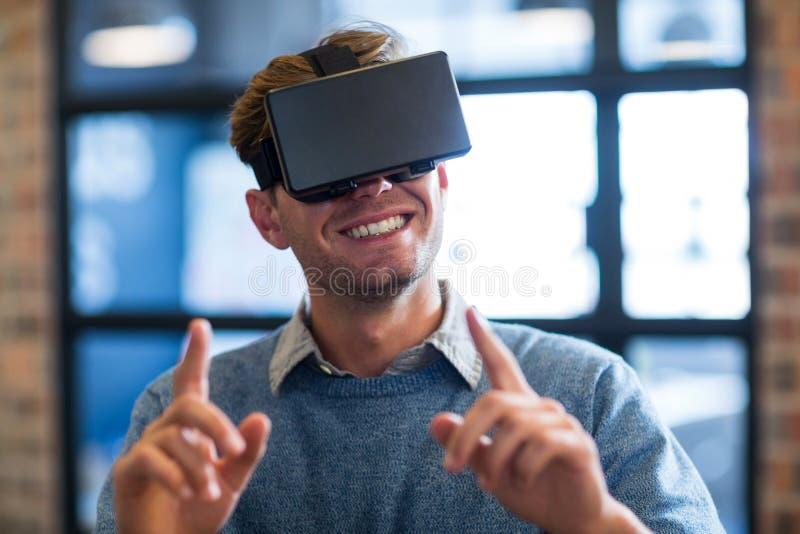 Hombre de negocios que gesticula mientras que usa las auriculares de la realidad virtual fotografía de archivo libre de regalías